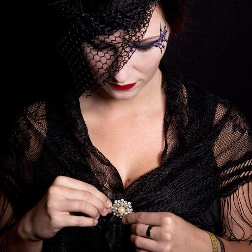Kombiniere ein schwarzes Kleid mit einer schicken Brosche