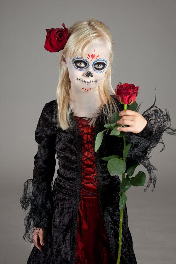 Mädchen mit Dia de los Muertos Make up an Halloween