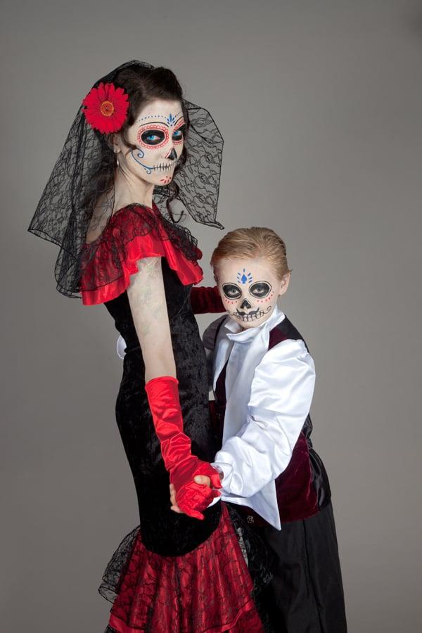 Mutter und Sohn im Dia de los Muertos Outfit wagen ein Tänzchen